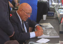 Fifty years after his near-fatal crash at Goodwood, Sir Stirling Moss signs copies of his book for fans