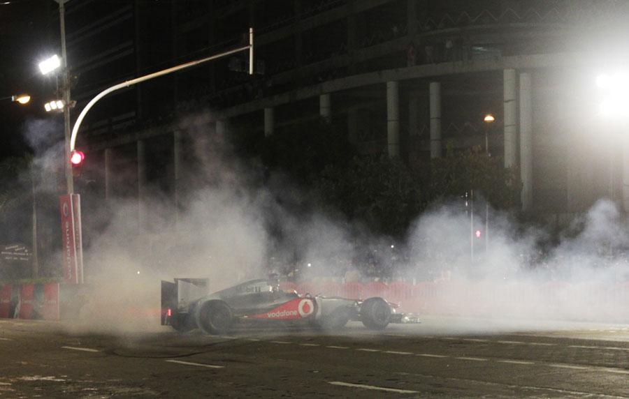 Lewis Hamilton displays a McLaren at an event for sponsor Vodafone in Mumbai