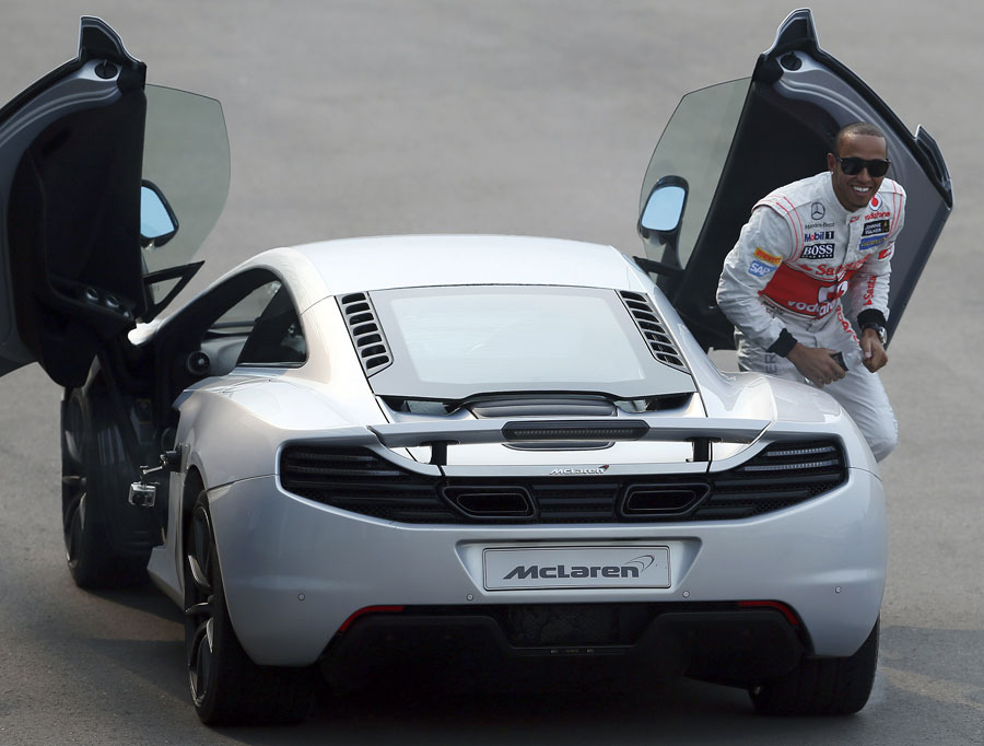 Lewis Hamilton is all smiles after performing burnouts in a McLaren MP4-12C at a promotional event