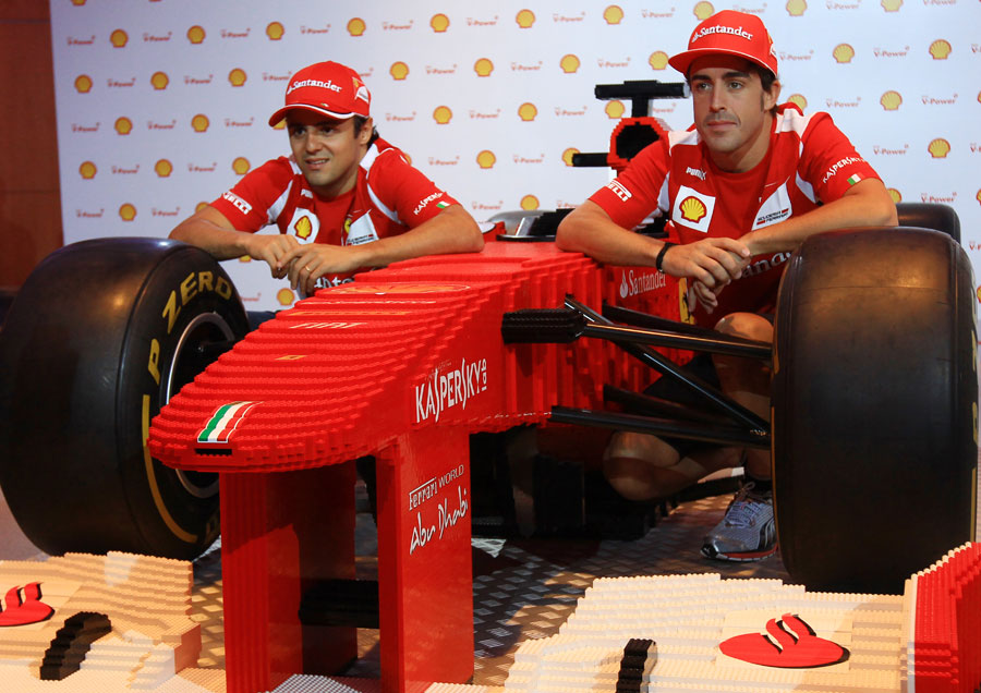 Felipe Massa and Fernando Alonso pose with a Lego Ferrari at a media event