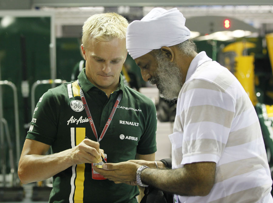 Heikki Kovalainen signs an autograph in the pit lane