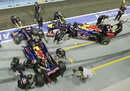 Sebastian Vettel and Mark Webber return to the Red Bull garages after practice