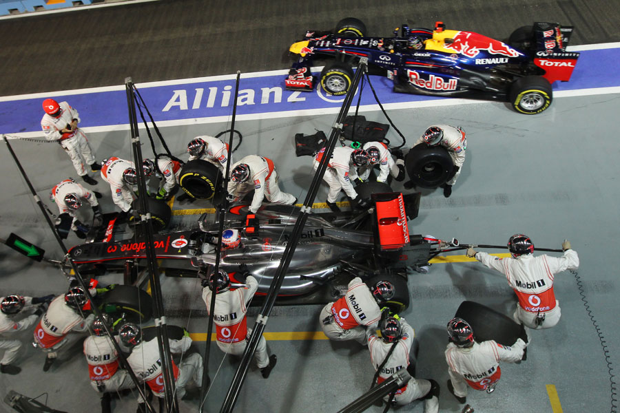 Jenson Button pits as Sebastian Vettel leaves his pit box