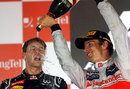 Jenson Button celebrates on the podium with race winner Sebastian Vettel