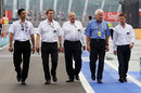 The FIA stewards and Charlie Whiting walk down the pit lane