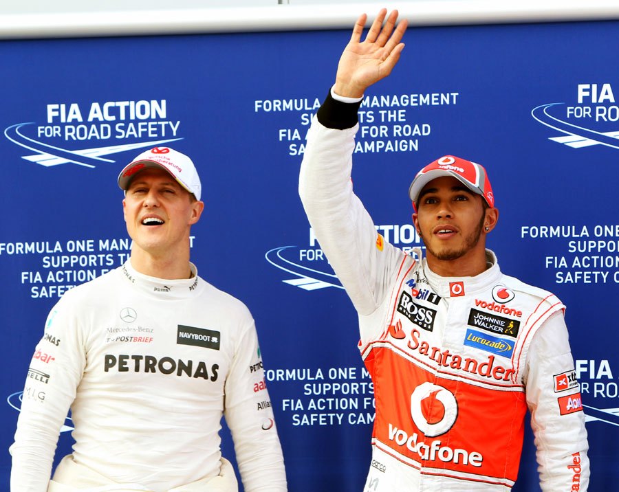 Lewis Hamilton celebrates his pole position with Michael Schumacher in parc ferme