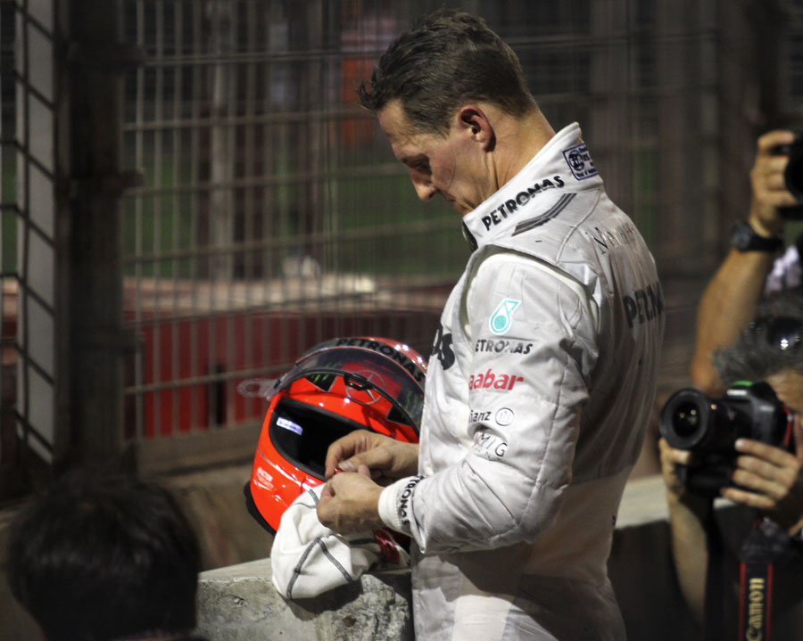 Michael Schumacher watches from the sidelines after crashing out of the race
