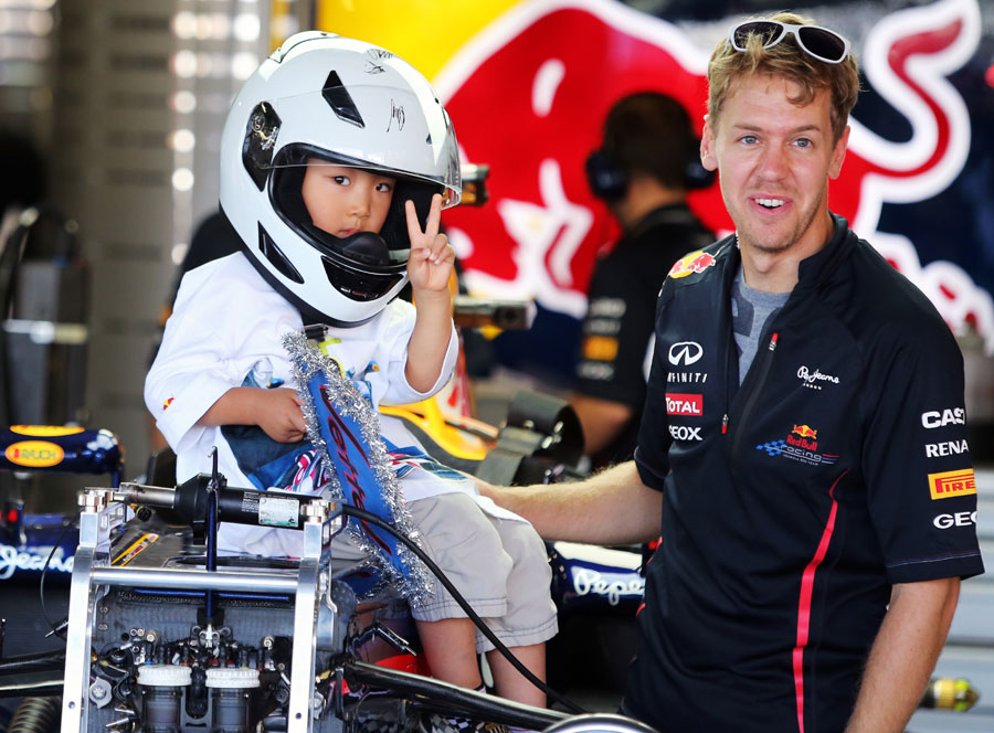 Sebastian Vettel gives a young fan a tour of the Red Bull garage