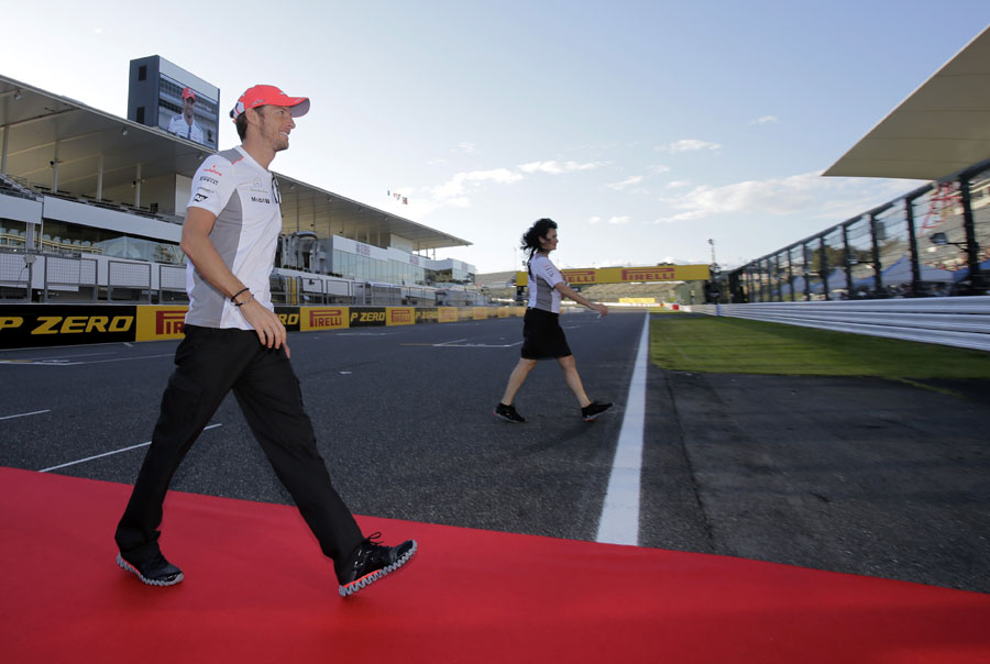Jenson Button crosses the circuit to greet fans in the main grandstand