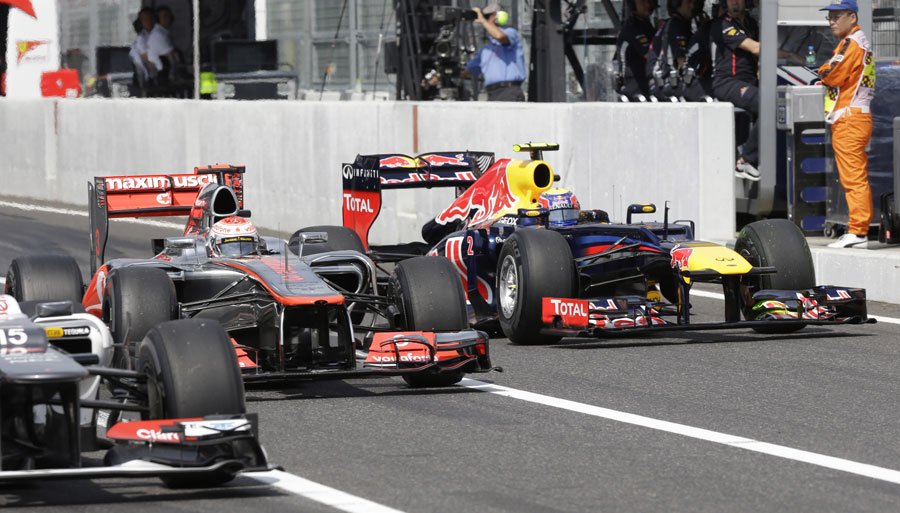 Mark Webber passes Jenson Button and Sergio Perez in the pit lane