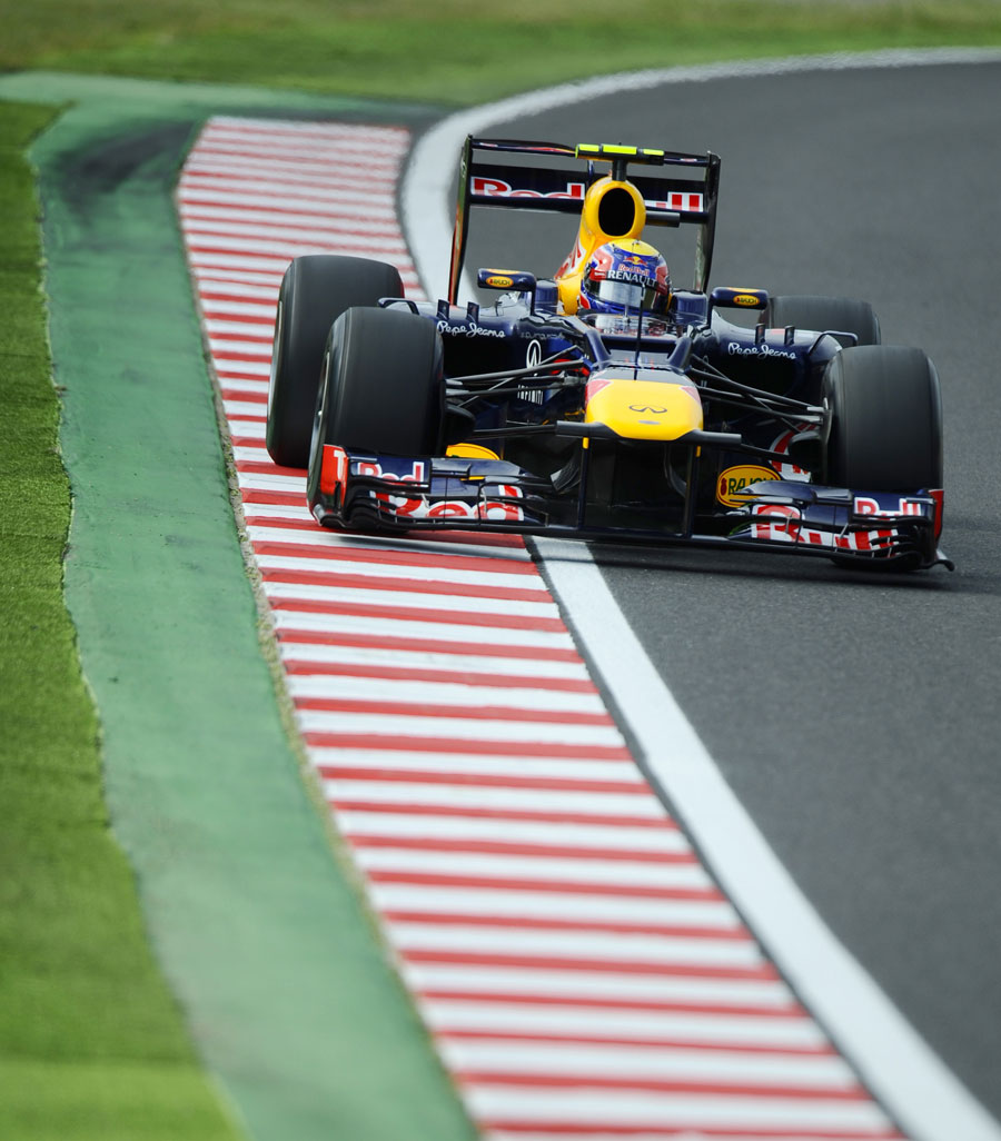 Mark Webber uses the kerbs on the exit of the corner