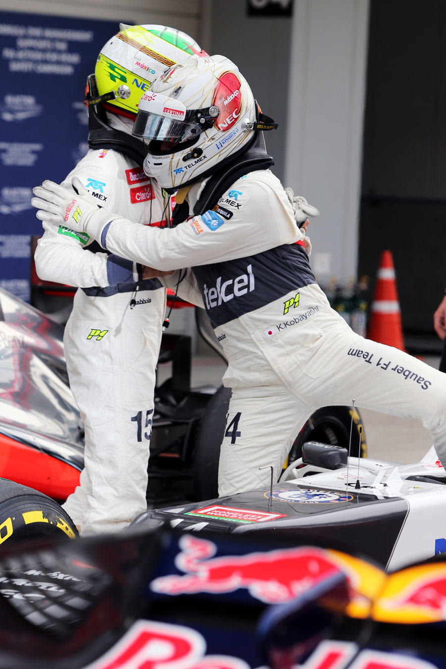 Kamui Kobayashi is congratulated by Sergio Perez in parc ferme