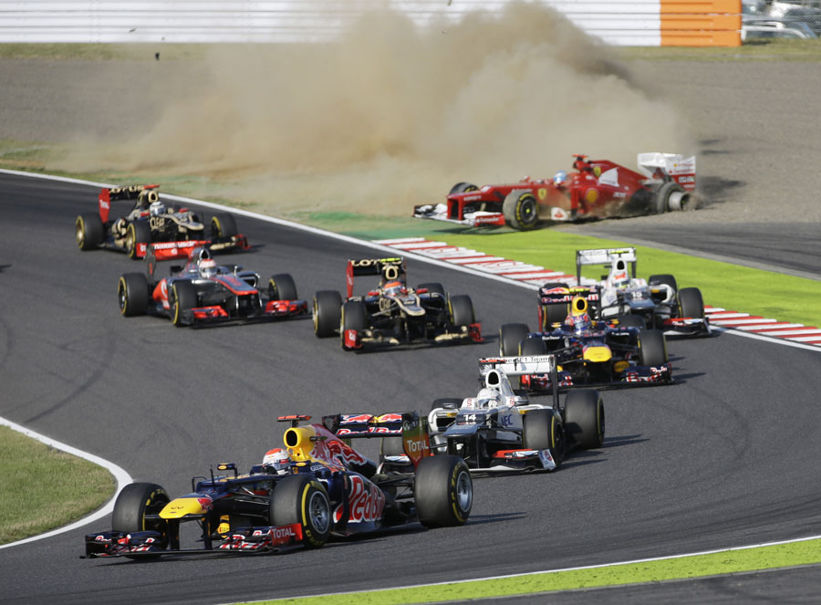 Sebastian Vettel leads as Fernando Alonso retires in the background at the start of the race
