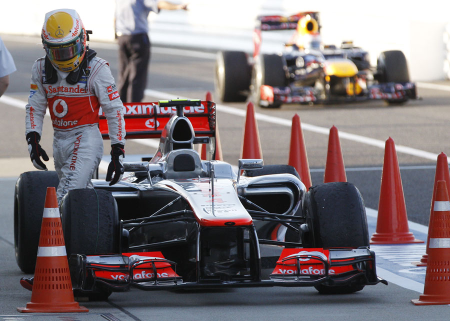 Lewis Hamilton gets out of his car as race winner Sebastian Vettel returns to the pits