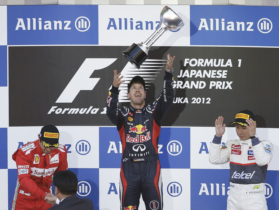 Sebastian Vettel celebrates his victory alongside Felipe Massa and Kamui Kobayashi on the podium