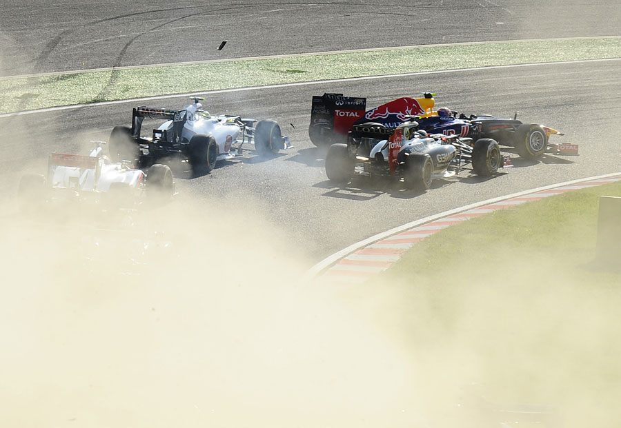 Romain Grosjean runs in to the side of Mark Webber in turn two