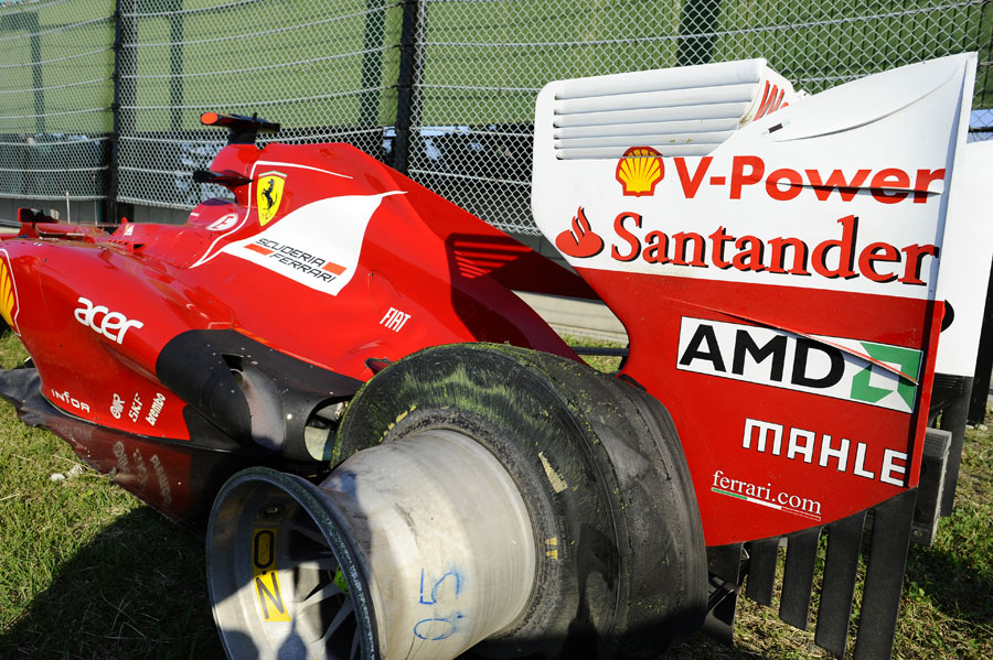 Fernando Alonso's Ferrari on the outside of turn one after he retired with a puncture