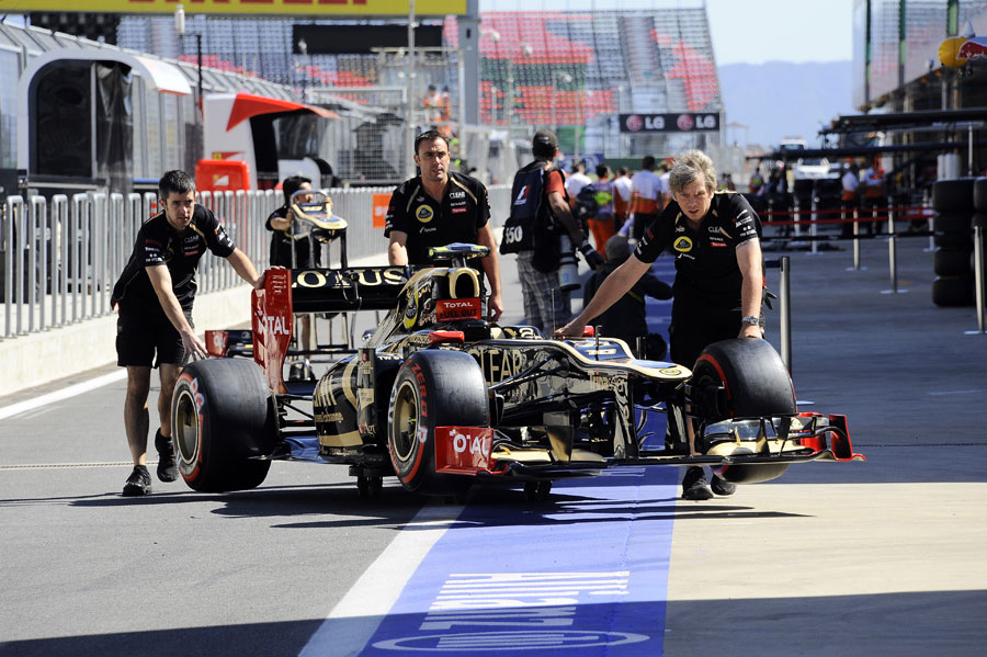 Lotus mechanics wheel the updated E20 through the pit lane