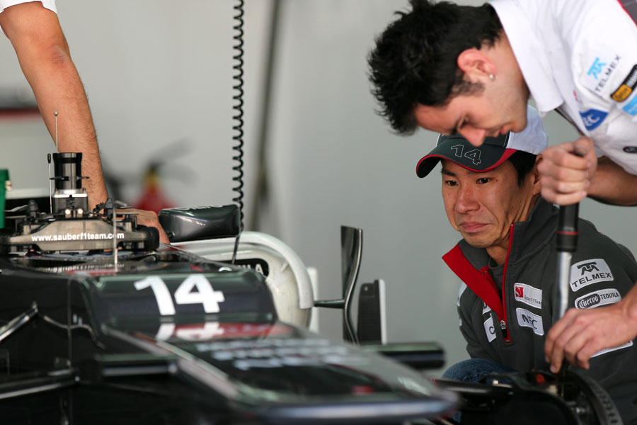 Kamui Kobayashi watches his mechanics prepare his car