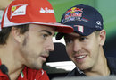 Sebastian Vettel and Fernando Alonso chat during the driver press conference