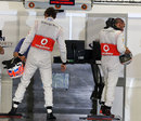 Jenson Button and Lewis Hamilton report to the FIA weighing scales after qualifying