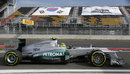 Nico Rosberg passes empty seats as he joins the track