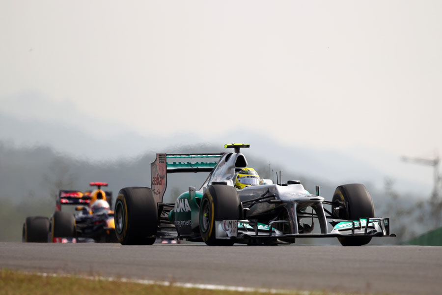 Nico Rosberg crests a hill with Sebastian Vettel close behind