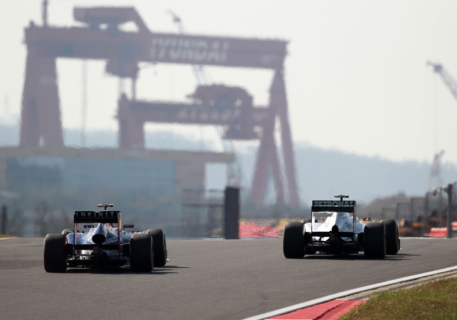 Mark Webber and Michael Schumacher crest a hill in the second sector