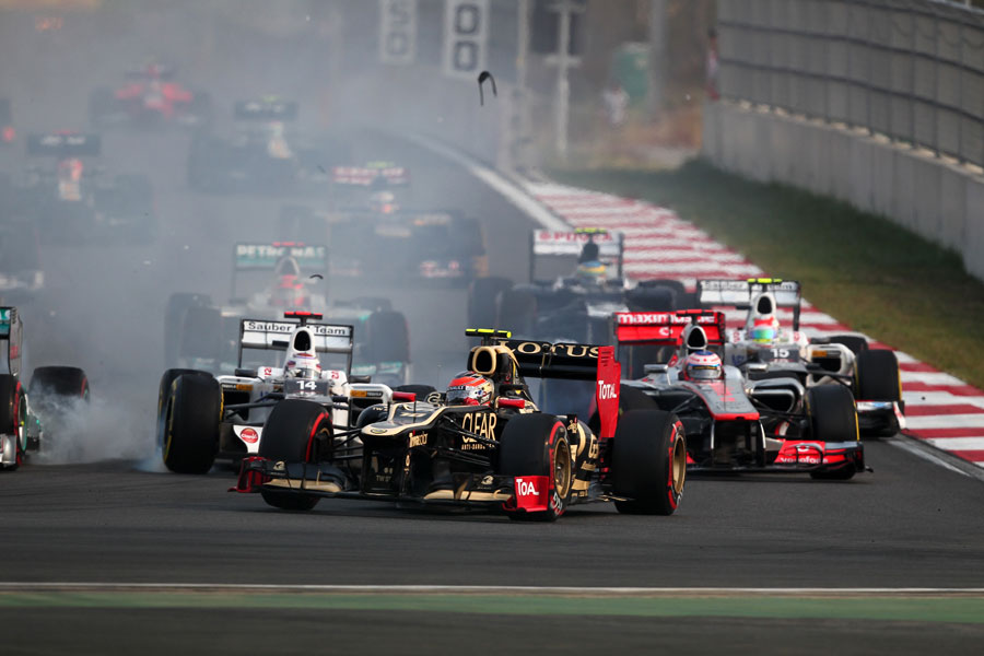 Romain Grosjean turns in to turn three ahead of the colliding Kamui Kobayashi and Jenson Button