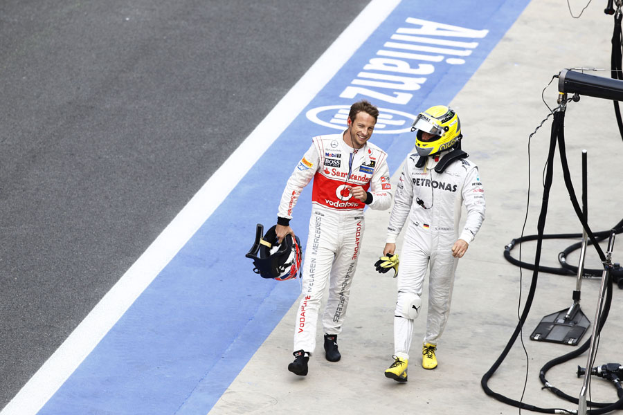 Jenson Button and Nico Rosberg walk back to the pits together after being taken out on lap 1