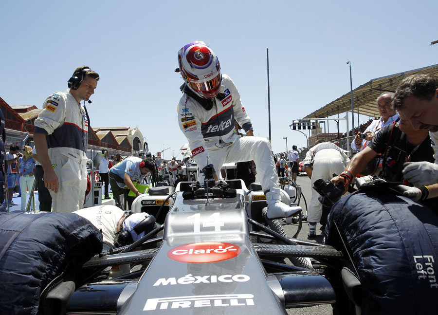 Kamui Kobayashi steps out of his car on the grid