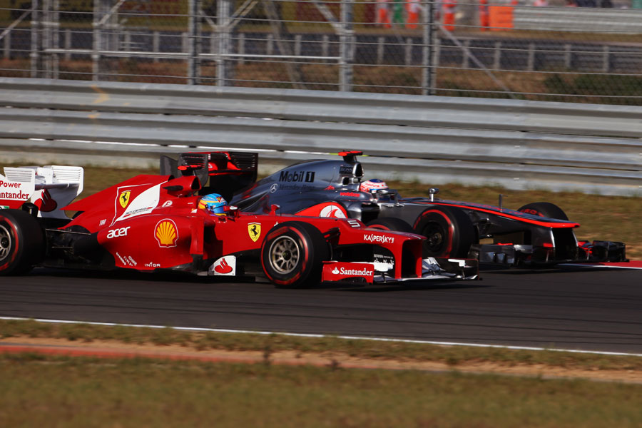 Fernando Alonso and Jenson Button vie for position on track