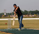 Mark Webber shows off his batting skills while facing the bowling of cricketer Gautam Gambhir