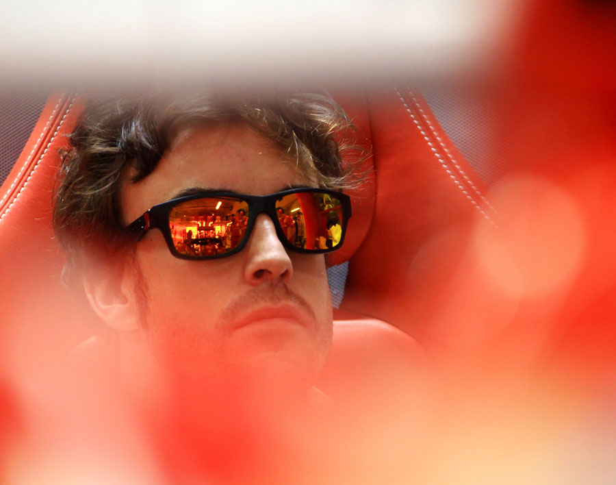 Fernando Alonso keeps an eye on work in the Ferrari garage