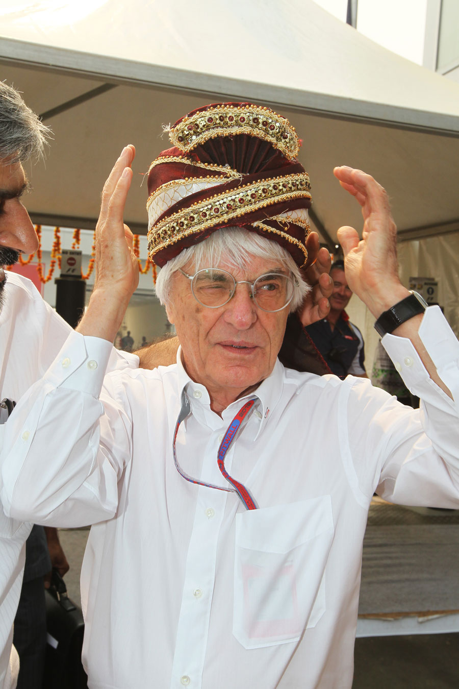 Bernie Ecclestone tries on a birthday present from Vicky Chandhok