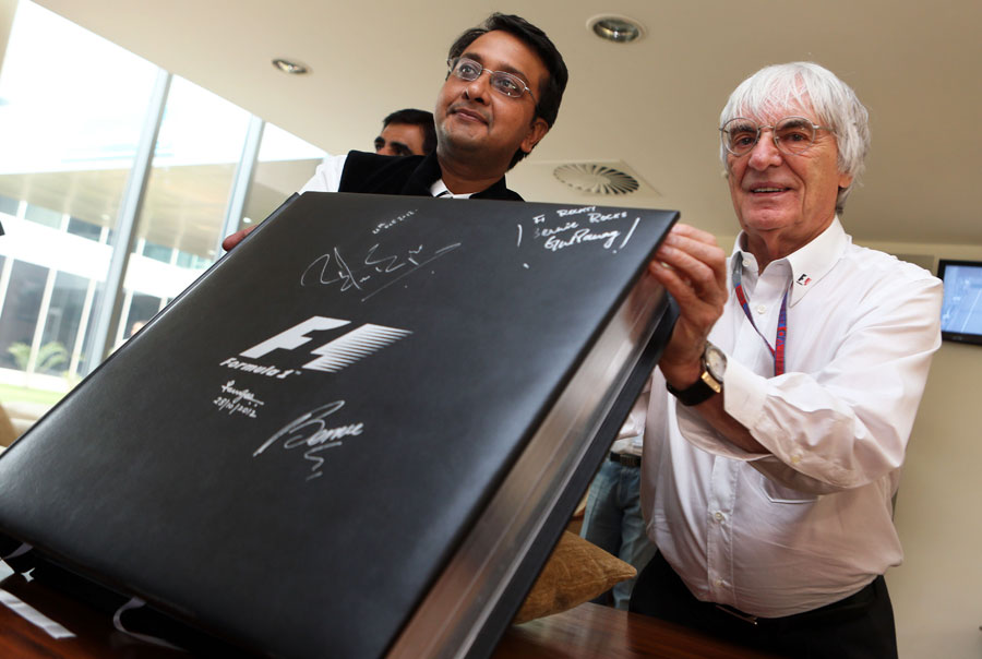 Bernie Ecclestone receives a large photo book on Formula One history as a present for his 82nd birthday