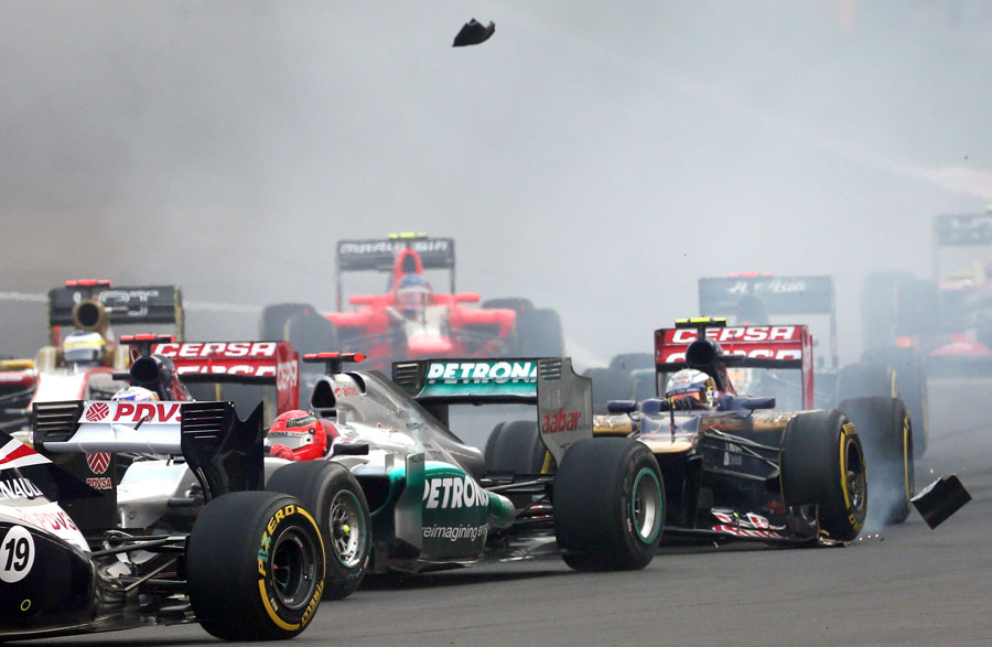 Jean-Eric Vergne loses part of his front wing against Michael Schumacher's Mercedes