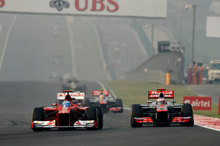 Fernando Alonso dives down the inside of Jenson Button in to turn four