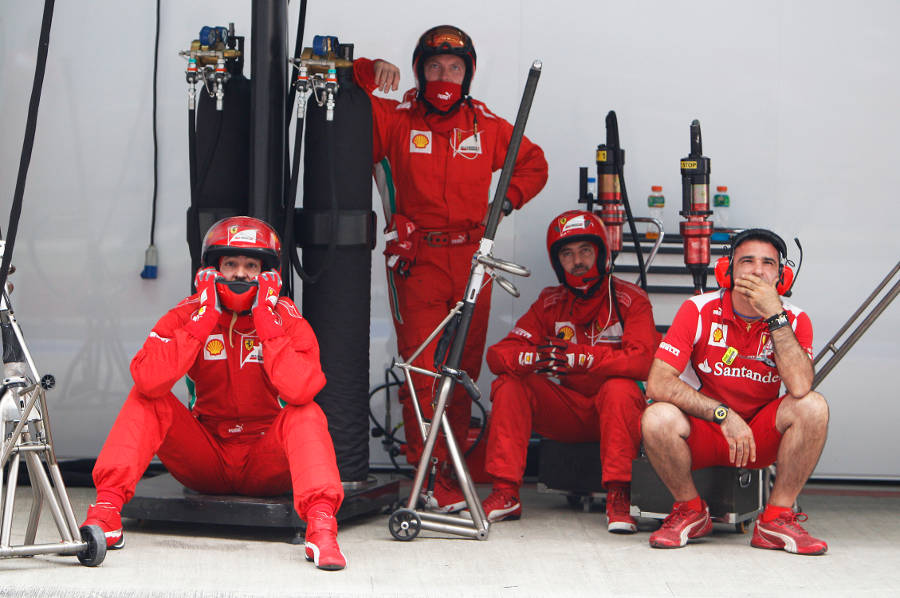 Ferrari mechanics watch on from the pit lane