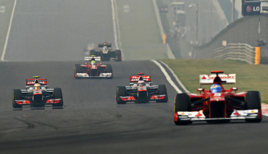 Lewis Hamilton and Jenson Button battle for position as Fernando Alonso chases down the Red Bulls