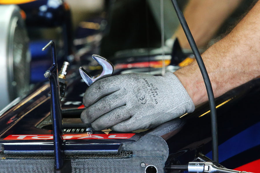 A mechanic makes adjustments to Mark Webber's Red Bull