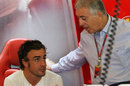 Fernando Alonso talks to Piero Ferrari, son of Enzo, at the back of the garage