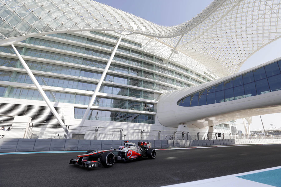 Jenson Button passes under the Yas Hotel during FP1