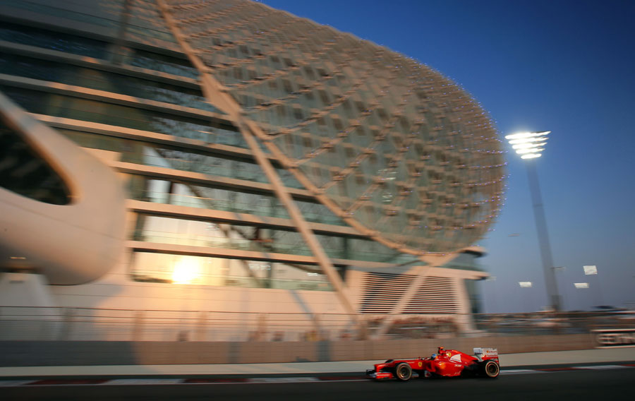 Fernando Alonso passes under the Yas Hotel