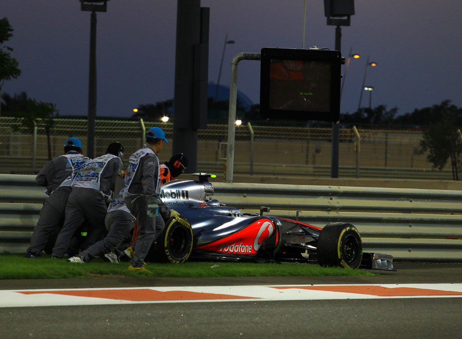 Lewis Hamilton's McLaren is pushed away by marshals after he retired from the lead