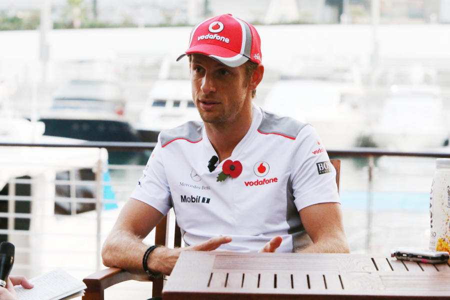 Jenson Button talks to the press in the paddock