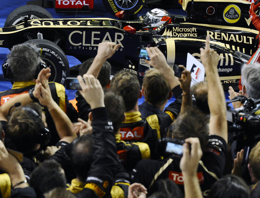 Kimi Raikkonen stops in parc ferme in front of a celebrating Lotus team
