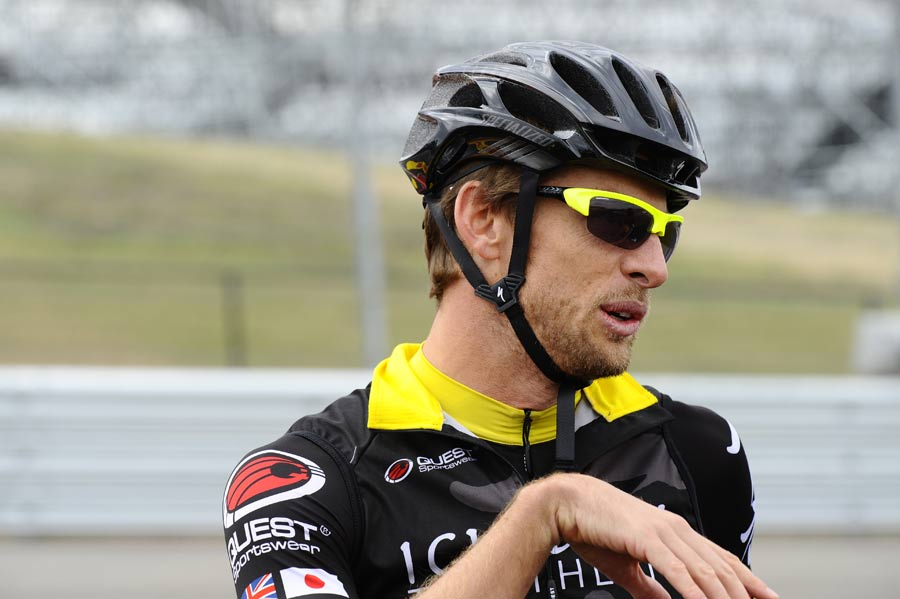 Jenson Button speaks to the media during a track ride