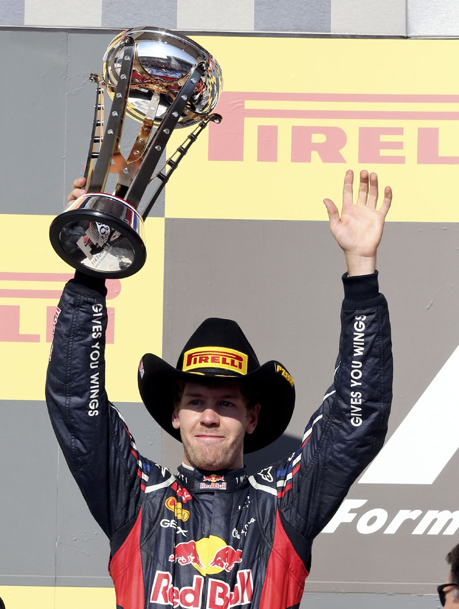 A stetson-wearing Sebastian Vettel celebrates on the podium