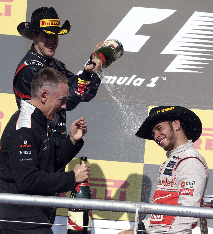 A stetson-wearing Sebastian Vettel sprays Martin Whitmarsh and Lewis Hamilton